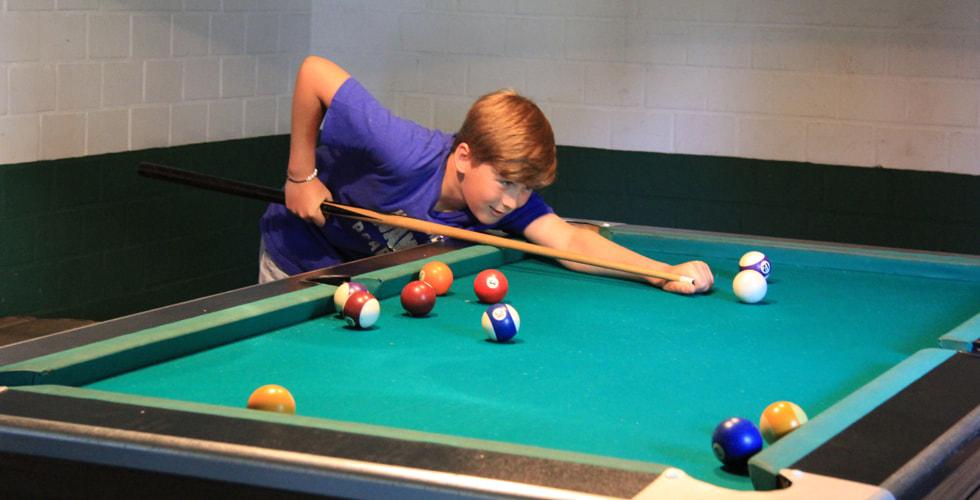 Junge spielt Billard