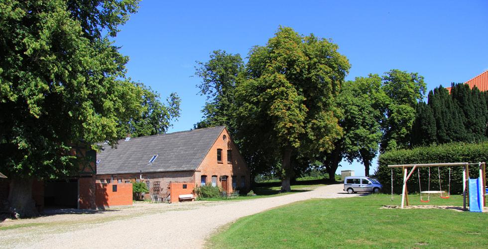 Überblick über den Gutshof mit Straße, Haus und Spielplatz
