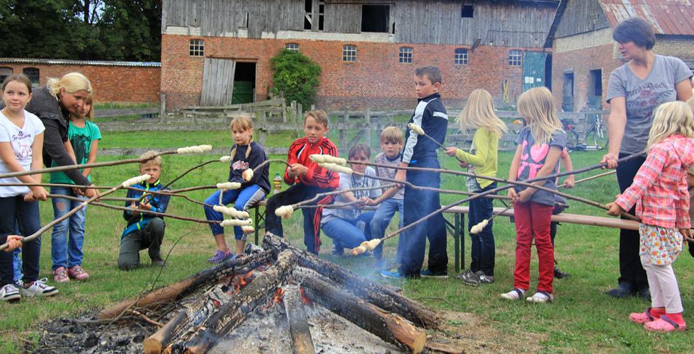 Kinder stehen um ein Lagerfeuer und backen ihr auf einem Stock befestigten Brotteig über dem Feuer