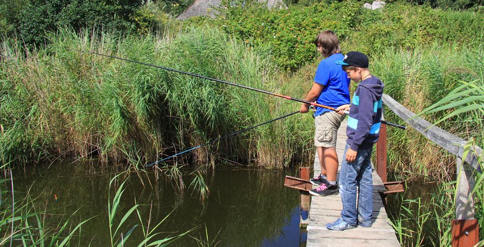 Zwei Jugendliche angeln von einem Steg aus